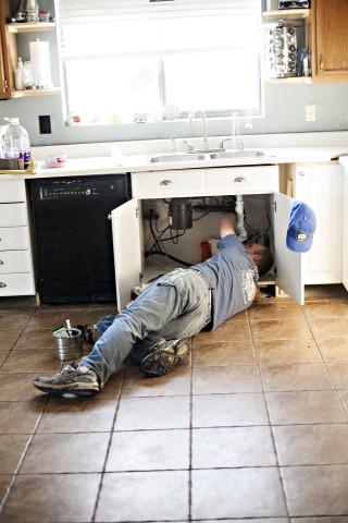 plumber repairing sink Plumbers Network